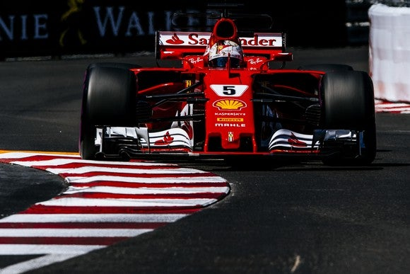 A red Ferrari Formula 1 race car rounding a corner on the race course in Monaco