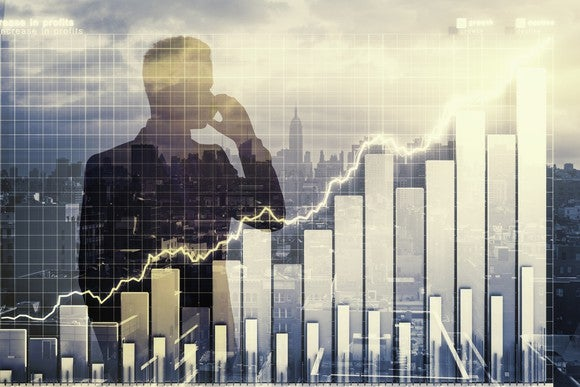 A businessman talks by phone, with a city skyline behind him. In front of him is an overlay of a rising stock chart.