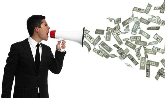 A businessman yells into a megaphone, with money coming out of it.
