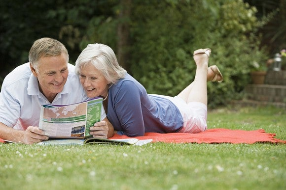 Senior couple reading on a picnic blanket