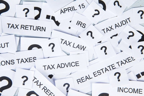 """Lots of pieces of paper, on which are written question marks and terms such as """"tax return"""" """"tax audit"""" and """"april 15."""""""