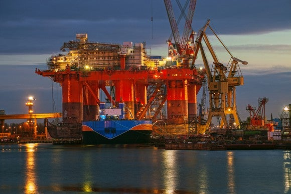 An offshore rig in a dockyard at night, with a waterway in the foreground.