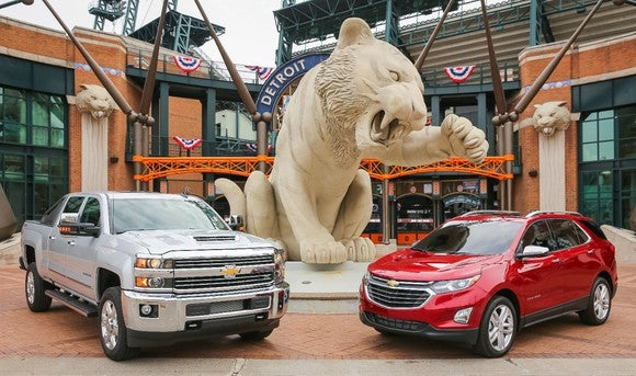 A Silver Ice Metallic 2018 Silverado 2500HD and a Cajun Red 2018 Equinox, parked side by side under a tiger statue at Comerica Park in Detroit.