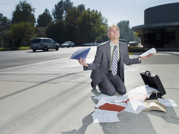 Frustrated businessman kneeling over a heap of unsorted papers.