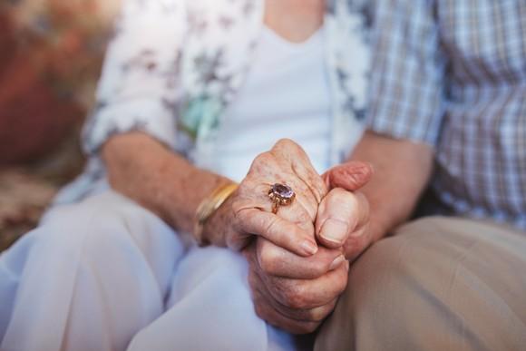 Senior couple holding hands.