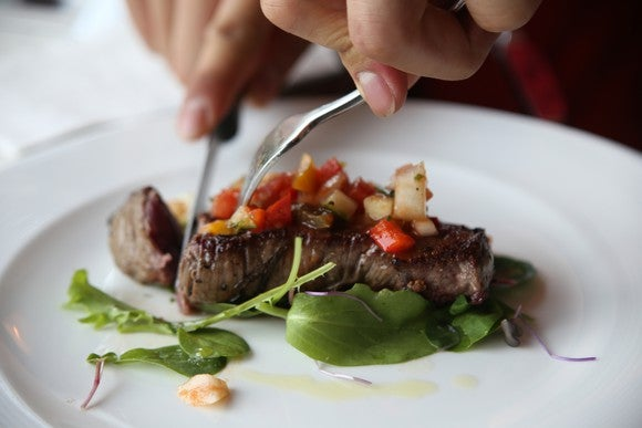 Eating a steak with salad.