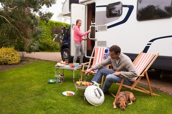 Family grilling in front of an RV