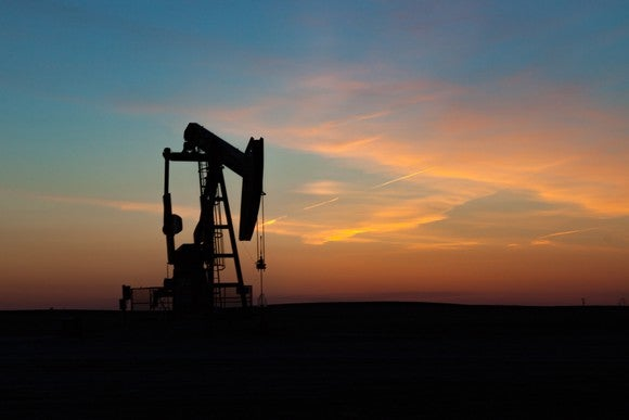 A single oil well pumpjack silhouetted against a prairie sunset.