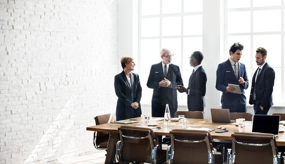 Executives standing around a boardroom table talking.