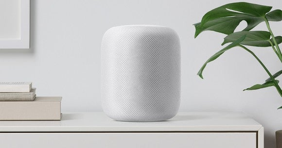 A white HomePod on a desk.