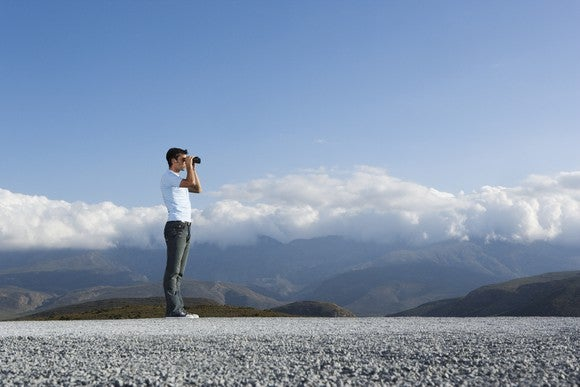 A man looks through binoculars, with a blue sky and mountains behind him.