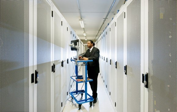 A worker on a computer stands amid rows of servers, like those used by internet giant Google and Facebook