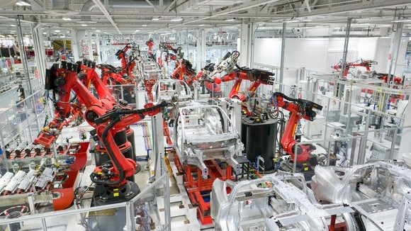Tesla car bodies are being manufactured on an assembly line.