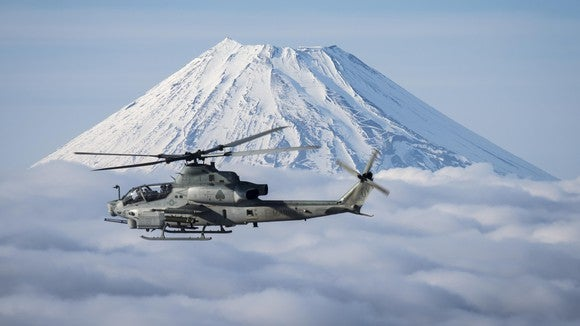 A Bell AH-1Z Viper flying in front of a mountain.