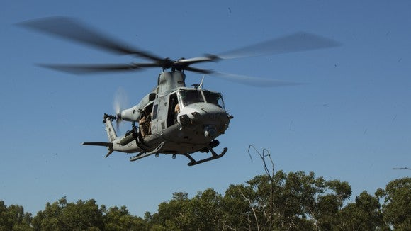 A UH-1Y Venom flying above the trees.