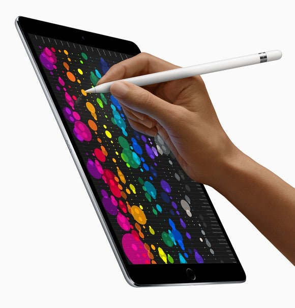 A person writes on an iPad Pro with an Apple pencil.