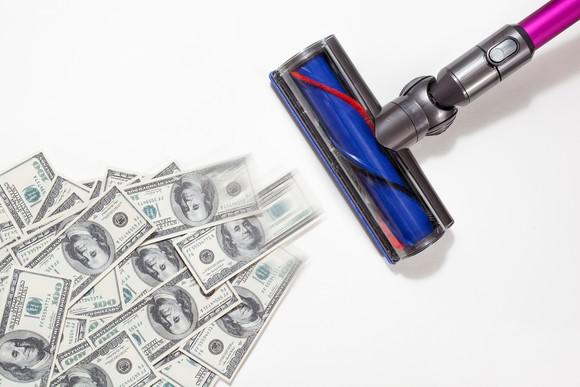 A vacuum sucking up dollar bills