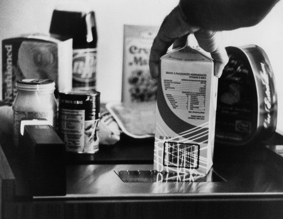 A black and white picture of a milk carton being scanned.