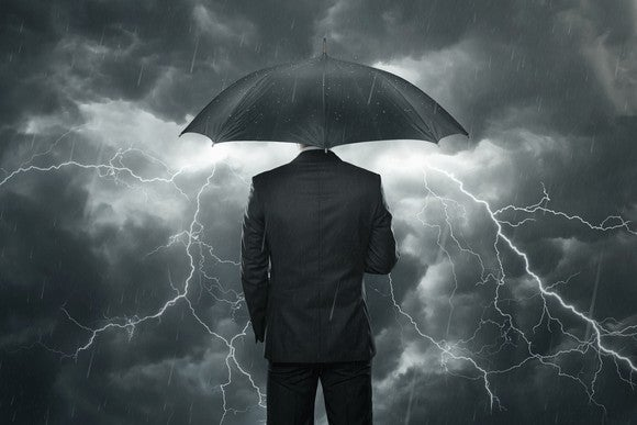 Businessman staying dry in a storm.