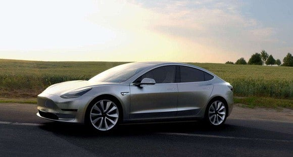 A Tesla Model 3 shown parked with a field in background.