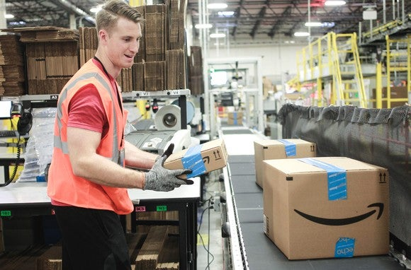 A worker holds an Amazon box as others come down a conveyor belt.