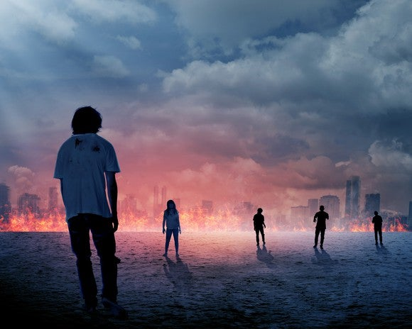 Zombies walking into a burning city.