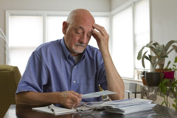 A man looks down with a worried expression at a stack of bills.