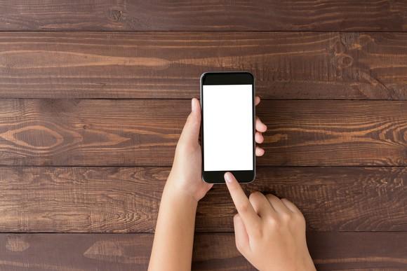 Hands holding smartphone against wooden backdrop