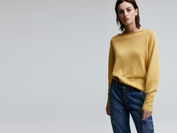 A woman wears a yellow shirt and blue jeans, as she stands against a plain background.