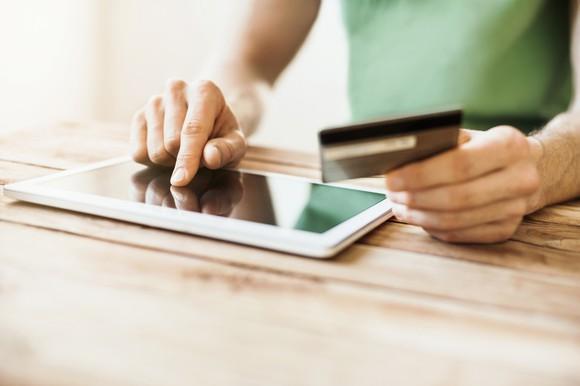 Man using tablet to buy something online.