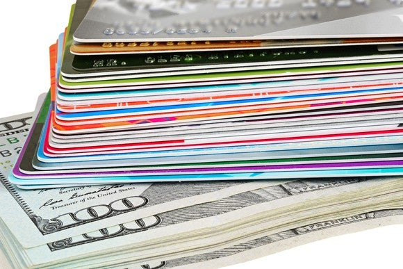 A pile of credit cards sits on top of a stack of hundred-dollar bills.