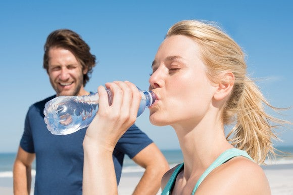 Woman runner drinking from water bottle on beach with male companion watching.