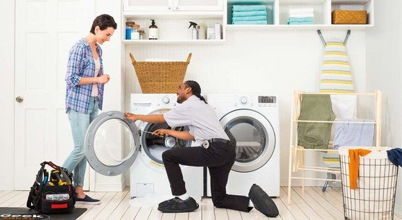 Best Buy Geek Squad employee installing washer dryer