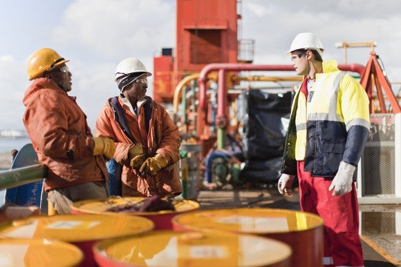 Three workers talk on an oil rig, with a group of oil barrels in the foreground.