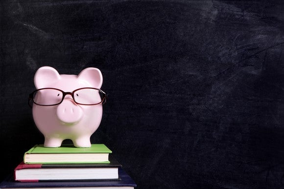 Wearing eyeglasses, a piggy bank stands on books in front of a chalkboard.