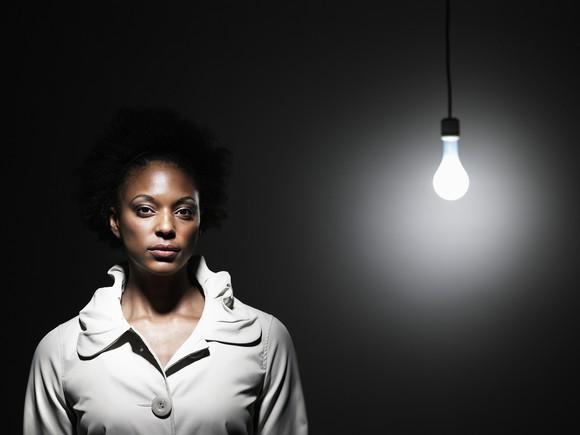 Woman standing near a light bare lightbulb.