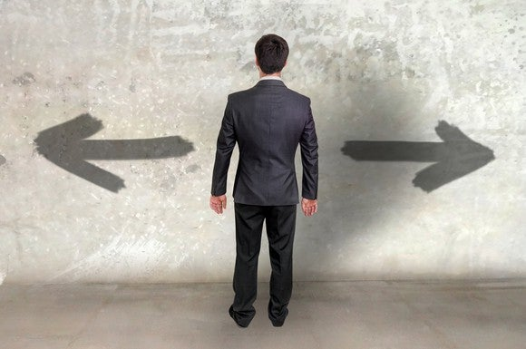 Businessman facing two arrows facing opposite directions