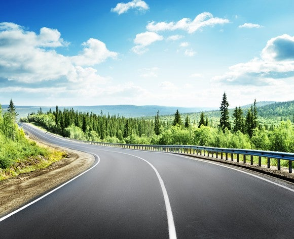 Long road stretching through forested mountains
