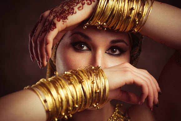 A woman flaunting a lot of gold bracelets on her wrists.
