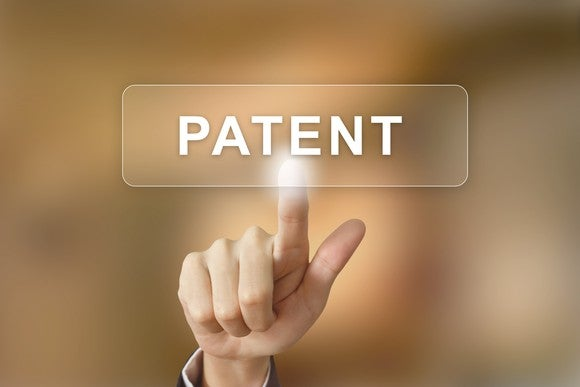 Hand pointing to patent button