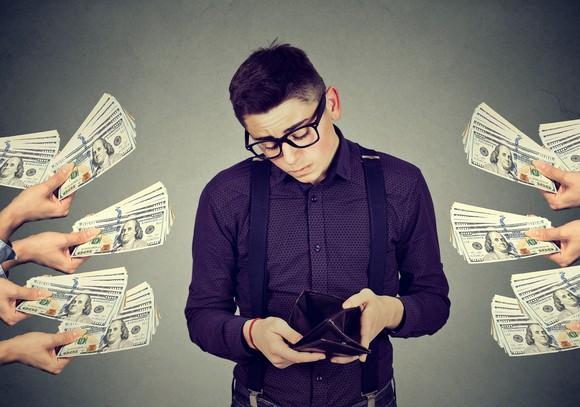 Man looking through wallet, ignoring cash bundles waved in his face.