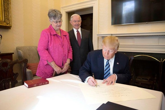 President Trump signing paperwork and flanked by Jeff Sessions and his wife.