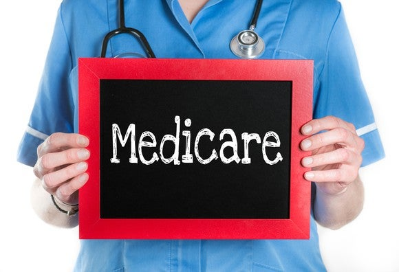 "A nurse holds a chalkboard with ""Medicare"" written on it."