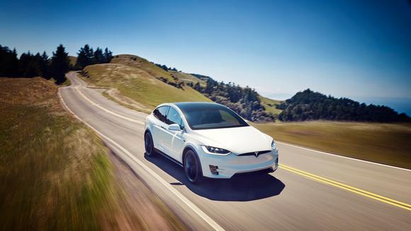 A white Tesla Model X driving downhill.