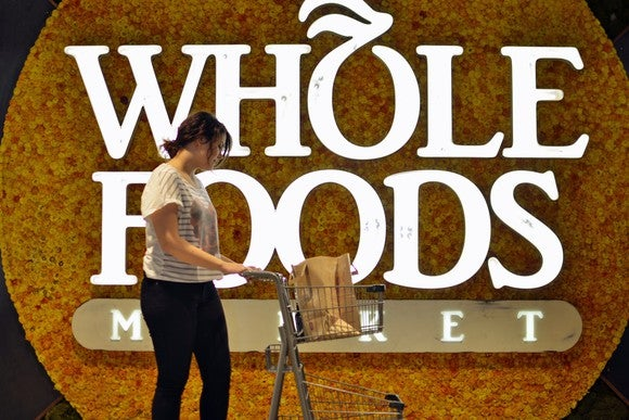 "A woman pushing a shopping cart in front of a ""Whole Foods"" sign"