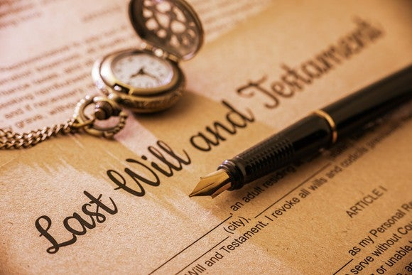 An ink pen rests on a will document, next to a pocket watch.