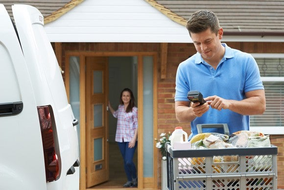 A man delivers an online order of groceries, while the recipient waits at her door.