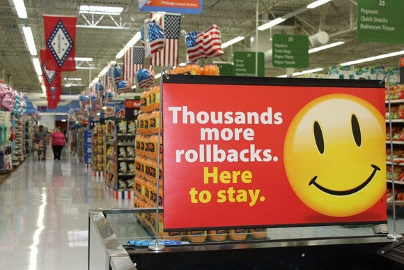 """A sign in a Walmart store features a yellow smiley face next to the words """"Thousands more rollbacks. Here to stay."""""""