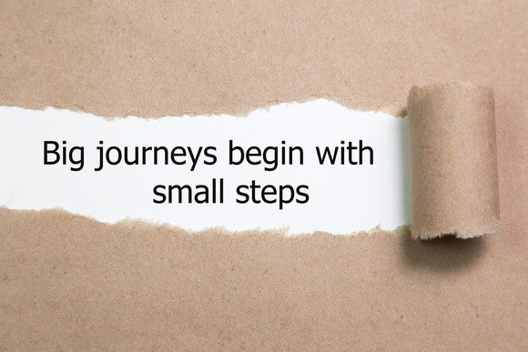 "The motivational quote ""Big journeys begin with small steps"" appears behind torn paper."