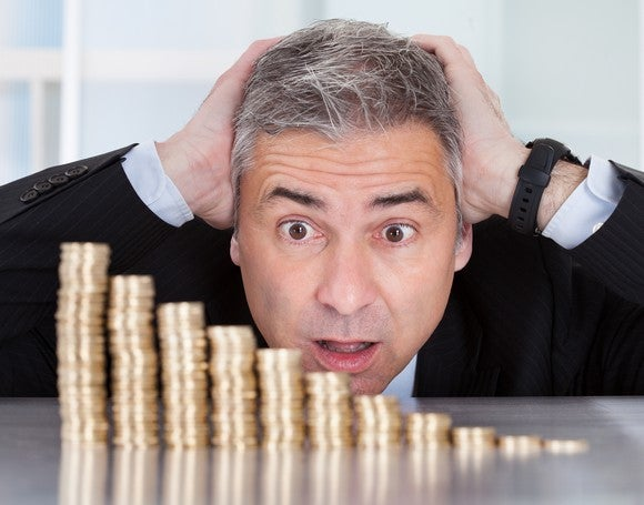 A declining stack of coins in front of a worried investor.